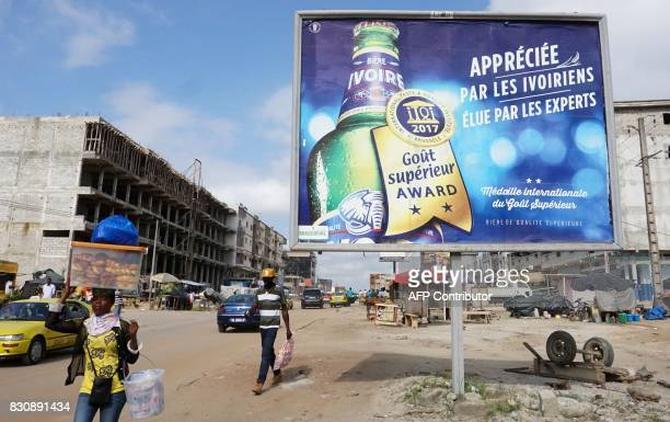 People walk past a billboard displaying an advertisement for Ivoire lager beer in Abidjan on July 13 2017 On posters and huge billboards around the...