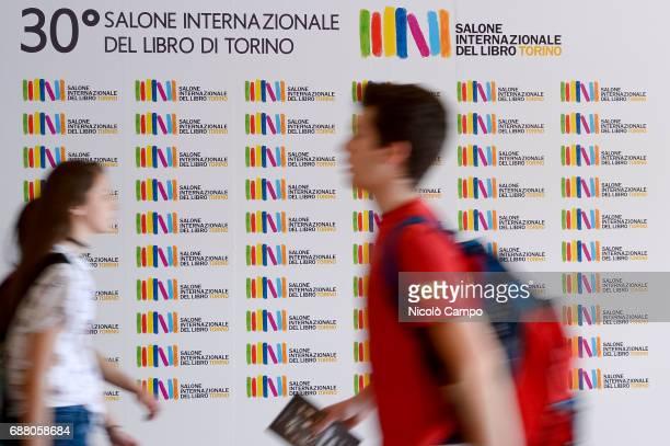 People walk past a billboard of the 30th Turin International Book Fair