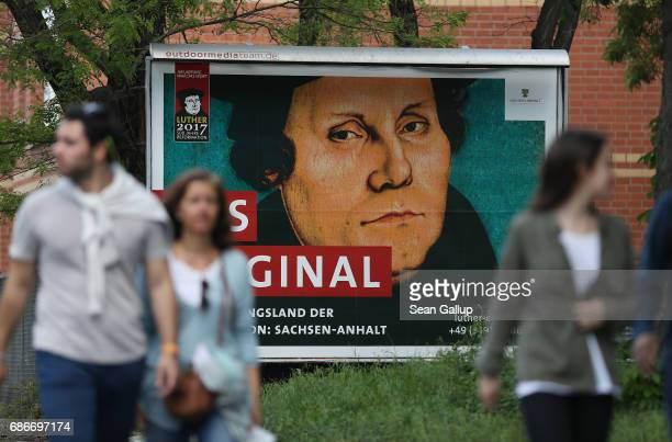 People walk past a billboard that shows 16thcentury religious reformer Martin Luther ahead of the Protestant Church Congress on May 22 2017 in Berlin...