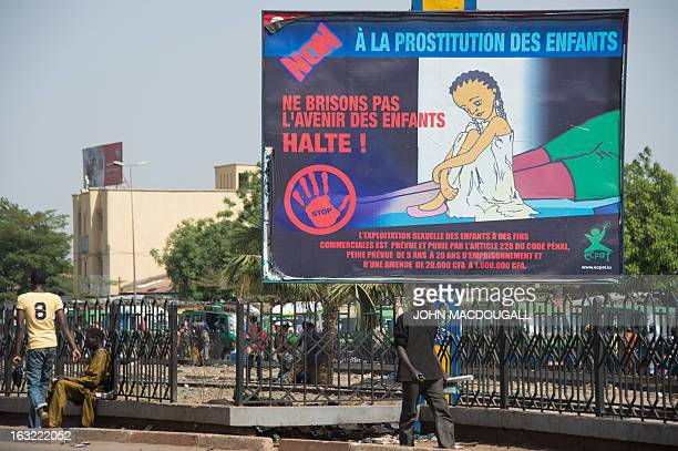 People walk past a billboard warning against child prostitution in Bamako on March 6 2013 AFP PHOTO / JOHN MACDOUGALL
