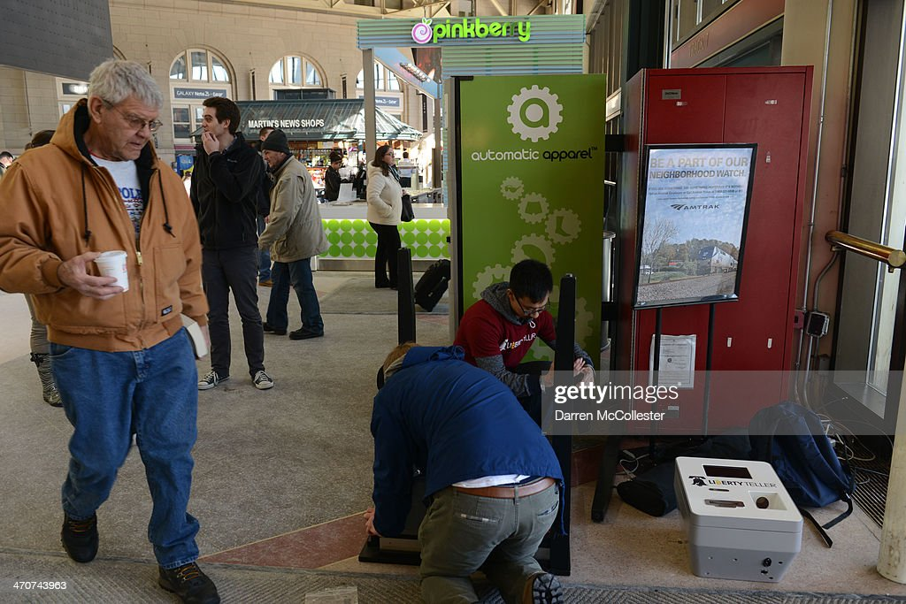 People walk past a Bitcoin ATM being installed at South Station February 20, 2014 in Boston, Massachusetts. The ATM was placed by Liberty Teller to help inform people about the digital currency, which can be bought and sold anonymously, and can be used at a number of online retailers in place of cash or credit cards.