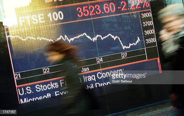 People walk past a Bloomberg market data display January 27 2003 in London United Kingdom The FTSE 100 index fell for the eleventh straight day as...