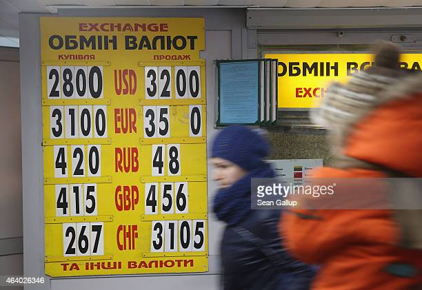 People walk past a board showing the day's exchange rates of the Ukrainian hryvnia against major currencies at a kiosk on February 21 2015 in Kiev...
