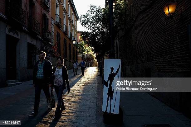 People walk past a board with a drawing of Don Quixote on near the Convento de las Trinitarias Descalzas on April 28 2014 in Madrid Spain The author...