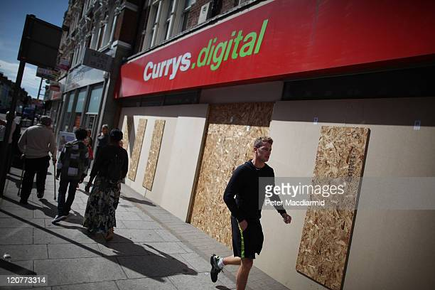 People walk past a boarded up Currys store in Clapham Junction on August 10 2011 in London England As trouble erupted through the night in other...
