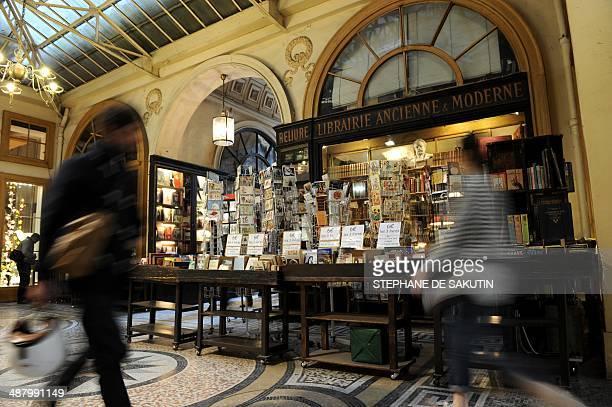 People walk past a bookshop at Galerie Vivienne in Paris on May 3 2014 AFP PHOTO / STEPHANE DE SAKUTIN