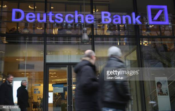 People walk past a branch of Deutsche Bank on January 17 2014 in Berlin Germany Banks across Europe will be announcing their financial results for...