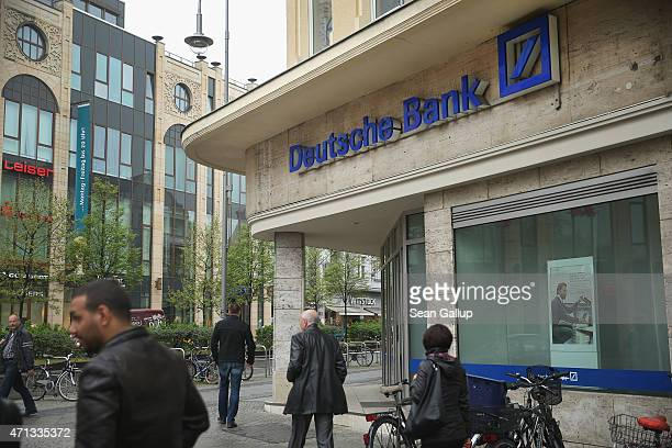 People walk past a branch of German bank Deutsche Bank on April 27 2015 in Berlin Germany Deutsche Bank announced earlier in the day that it will...