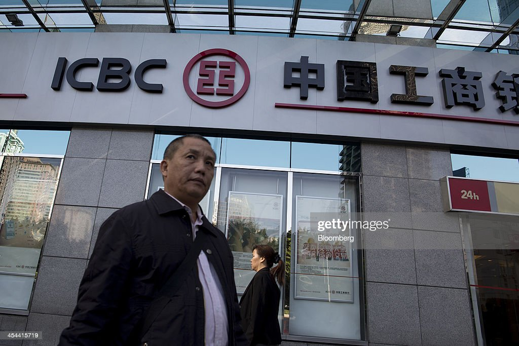 People walk past a branch of Industrial & Commercial Bank of China Ltd. (ICBC) in the Tianhe district of Guangzhou, Guangdong province, China, on Monday, Nov. 25, 2013. China is proposing the largest package of economic reforms since the 1990s to stoke growth in the worlds biggest emerging market. Photographer: Brent Lewin/Bloomberg via Getty Images