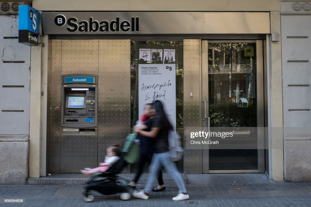 People walk past a branch of Spain's Banco de Sabadell bank on October 5, 2017 in Barcelona, Spain. Tension between the central government and the Catalan region have increased after last weekend's independence referendum. Spanish shares and bonds have been hit hard since the political turmoil with fears Spain could be on the brink of a financial crisis should the civil unrest continue. Two of Spain's largest banks, Banco de Sabadell and CaixaBank have both held meetings discussing steps to transfer their registered headquarters to other cities in Spain. The Spanish government suspended the Catalan parliamentary session planned for Monday in which a declaration of independence was expected to be made.
