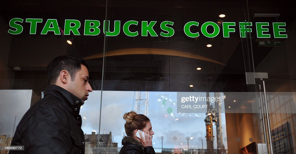 People walk past a branch of Starbucks in central London on February 1, 2013. Despite pledging to pay millions of pounds in extra tax in Britain, Starbucks faces a battle to restore its reputation over its fiscal stance, with analysts saying the offer is 'too little too late'.
