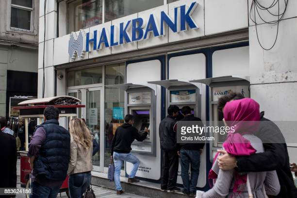 People walk past a branch of Turkish bank HalkBank on December 1 2017 in Istanbul Turkey The trial of Mr Reza Zarrab an IranianTurk who ran a foreign...