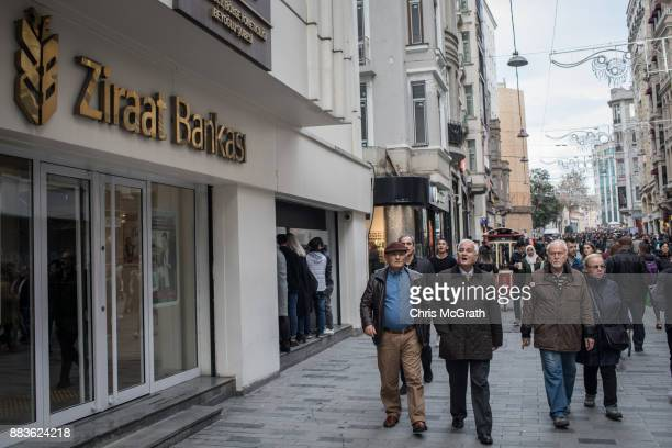 People walk past a branch of Turkish bank Ziraat Bank on December 1 2017 in Istanbul Turkey The trial of Mr Reza Zarrab an IranianTurk who ran a...