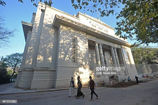People walk past a building in downtown Yangon where Myanmar's government hopes to locate the country's first stock exchange on January 14 2014...