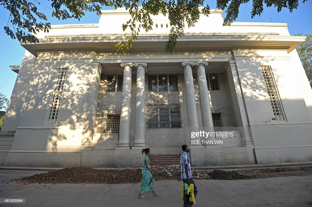 People walk past a building in downtown Yangon where Myanmar's government hopes to locate the country's first stock exchange in Yangon on January 14...