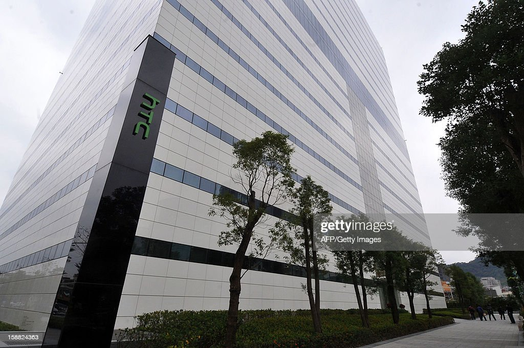 People walk past a building of Taiwan's HTC during as a press conference takes place to release their 2013 corporate image advertising in New Taipei City on December 31, 2012. Taiwan's HTC unveiled a new smartphone 'HTC butterfly' boasting a higher resolution display than iPhone5 on the island on December 11, 2012. AFP PHOTO / Mandy CHENG
