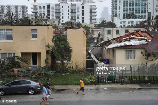 People walk past a building where the roof was blown off by Hurricane Irma on September 10 2017 in Miami Florida Hurricane Irma which first made...