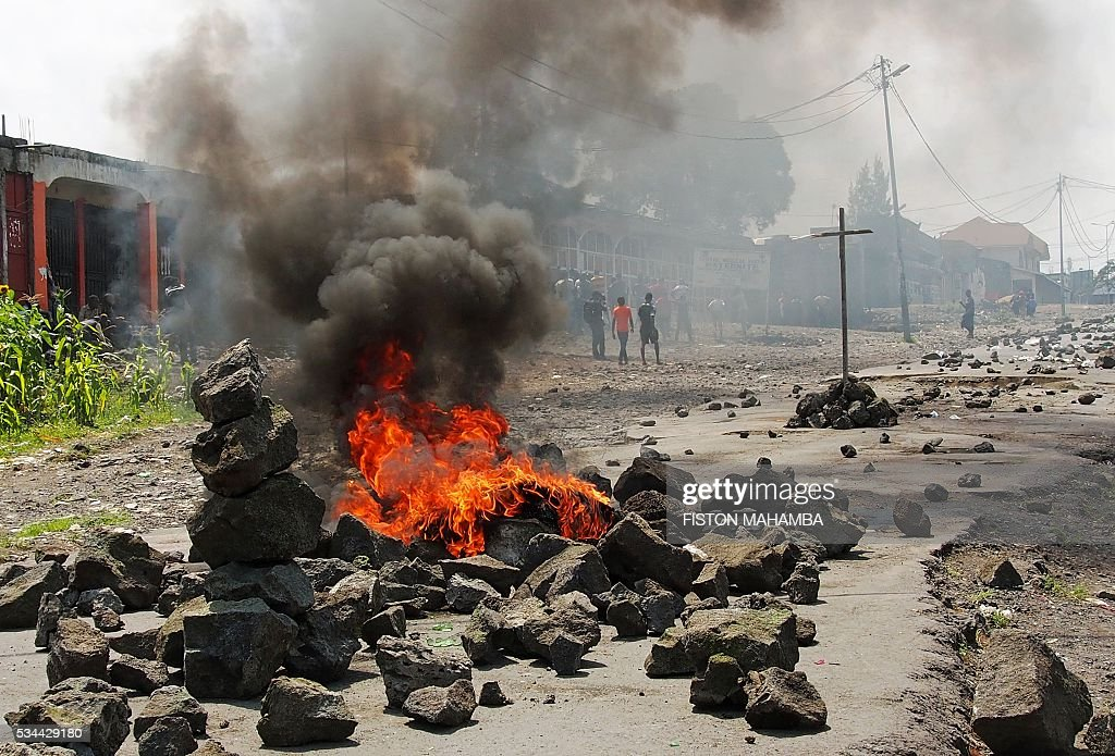 People walk past a burning barricade during a nationwide protest against long-serving President Joseph Kabila, in Goma, on May 26, 2016. Congolese security forces fired tear gas and charged at several thousand stone-throwing protesters in the capital Kinshasa Thursday as nationwide rallies against veteran President Joseph Kabila turned violent. Large numbers of riot police were deployed across the Democratic Republic of Congo for the protests called by three opposition groups in defiance of government bans. / AFP / FISTON