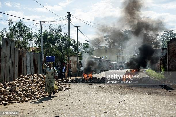 People walk past a burning barricade on a street in Bujumbura on May 14 2015 after a night marked by gunfire and explosions in various areas of the...