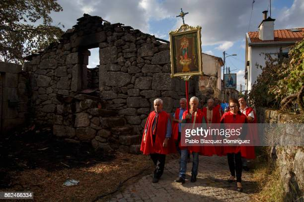 People walk past a burnt house during the funeral of a victim of a wildfire in the village of Vila Nova near Vouzela on October 17 2017 in Viseu...