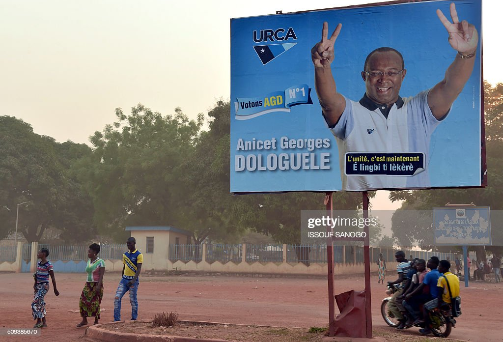 People walk past a campaign poster of Central African Republic second round presidential candidate Anicet Georges Dologuele in a street of Bangui on February 10, 2016, ahead of the Febuary 14 presidential and legislatives elections. The deferred presidential run-off, delayed due to organisational problems, and postponed legislative election, rescheduled after annulment due to irregularities, have been widely seen as turning a page on the worst sectarian violence in the traditionally unstable and dirt poor nation. / AFP / ISSOUF SANOGO
