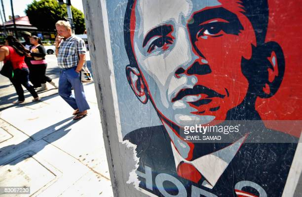 People walk past a campaign poster of US Democratic presidential candidate Illinois Senator Barack Obama in Los Angeles on September 30 2008 Obama...