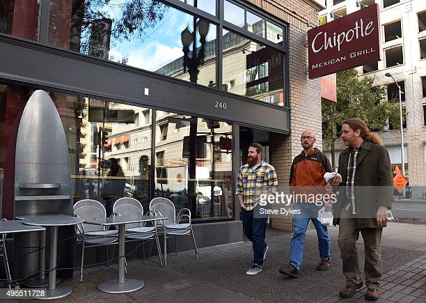 People walk past a Chipotle Mexican Grill store location in downtown Portland on November 3 2015 in Portland Oregon Chipotle Mexican Grill is...