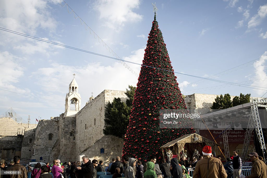 People walk past a Christmas tree outside the Church of the Nativity, traditionally believed to be the birthplace of Jesus Christ, on December 25, 2013 in Bethlehem, West Bank. Every Christmas pilgrims travel to the church where a gold star embedded in the floor marks the spot where Jesus was believed to have been born.