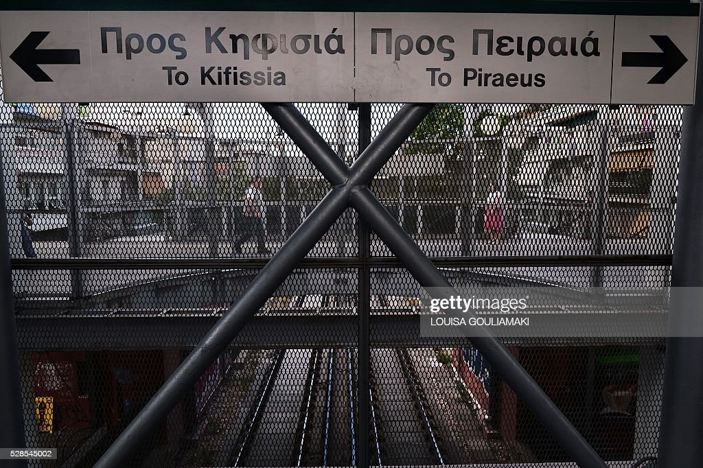 People walk past a closed urban railway station in Athens, during a 48-hours public transport strike in Athens, on May 6, 2016. Greece's labour unions stage a two-day general strike to protest against controversial government plans to overhaul pensions and increase taxes to meet demands of its bailout creditors. / AFP / LOUISA