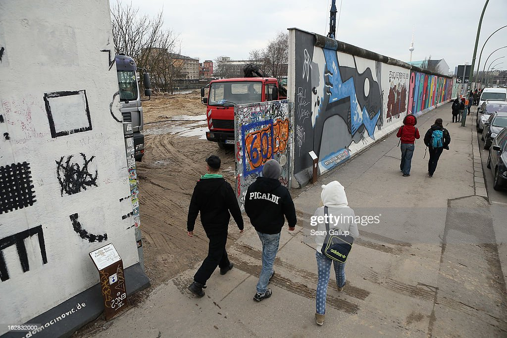 People walk past a construction site next to the East Side Gallery, which is the longest still-standing portion of the former Berlin Wall, where a new hotel is scheduled to be built on February 28, 2013 in Berlin, Germany. According to media reports the developer in charge of the project plans to remove an approximately 25-meter long piece of the Wall and transfer it elsewhere in order to allow access to the construction site. Critics, including East Side Gallery mural artists and Spree River embankment development opponents, decry the move, citing the East Side Gallery's status as a protected landmark and a majortourist attraction.
