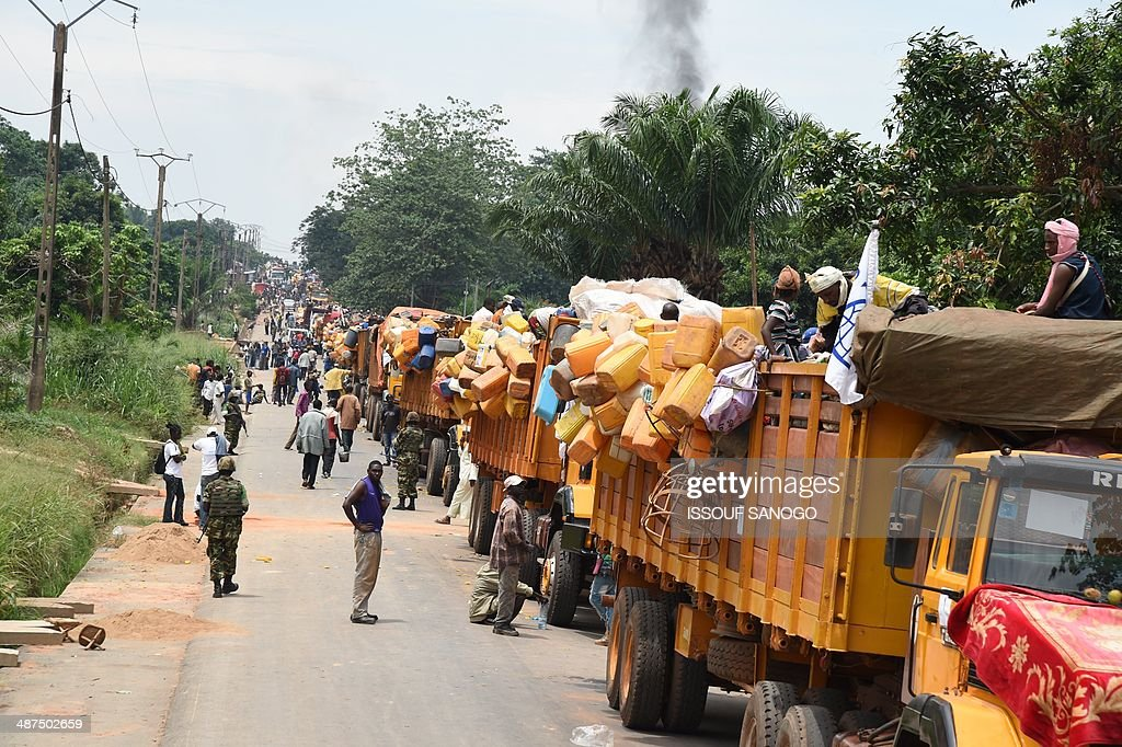 People walk past a convoy of vehicles taking Muslims from the PK12 district, north of Bangui, to the north of the country, on April 27, 2014. About 1,300 Muslims who were hiding on the outskirts of Bangui, and were frequently attacked by predominantly Christian militias, left Bangui on April 27 in an impressive convoy escorted by the Misca African force, to relocate north of the country. AFP PHOTO / ISSOUF SANOGO