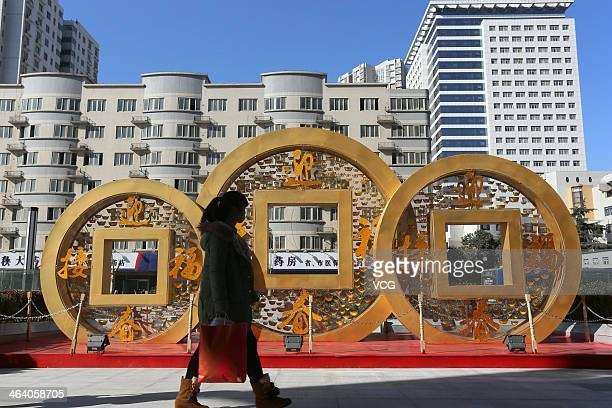 People walk past a copper coinshapped decoration for Chinese New Year on January 20 2014 in Zhengzhou China China's economy expanded 77 percent...
