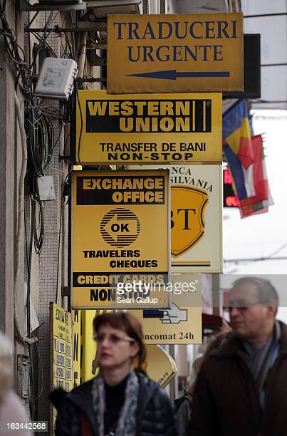 People walk past a currency exchange and Western Union office on March 7 2013 in Bucharest Romania Both Romania and Bulgaria have been members of the...