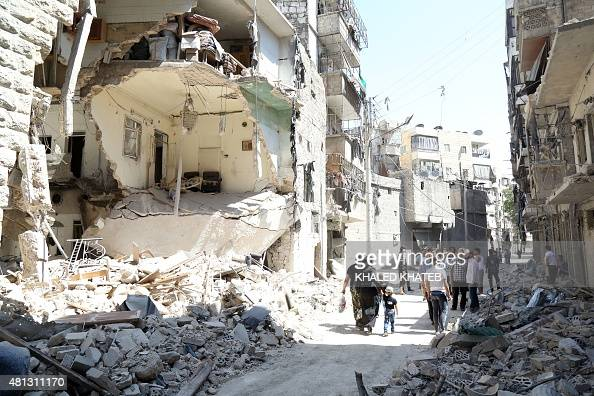 People walk past a damaged building in the alKalasa neighbourhood of the northern Syrian city of Aleppo on July 19 2015 AFP PHOTO / AMC / KHALED...