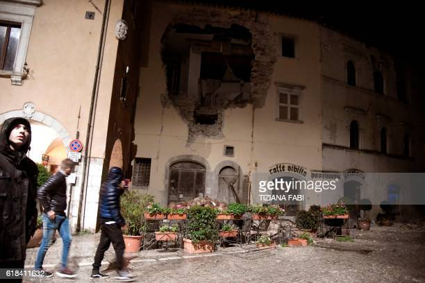 People walk past a destroyed building in the village of Visso central Italy after earthquakes on October 26 2016 Twin earthquakes rocked central...