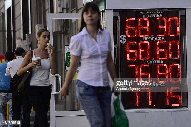 People walk past a digital information board showing exchange rates of the Russian rouble against the US Dollar and the Euro outside a bureau de...
