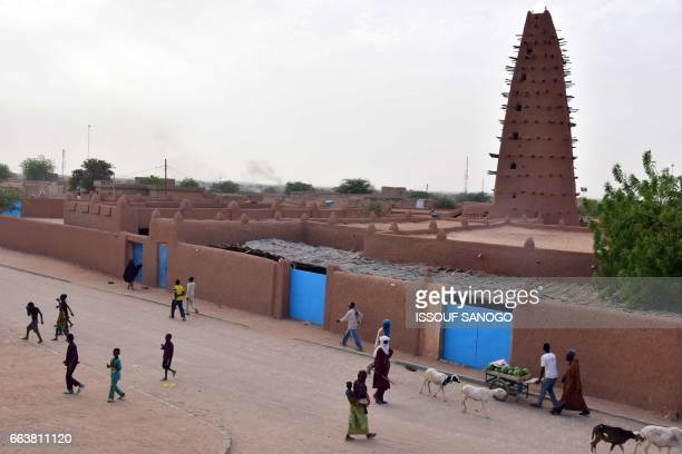 People walk past a earthen mud mosque in Agadez in northern Niger on April 2 2017 / AFP PHOTO / ISSOUF SANOGO