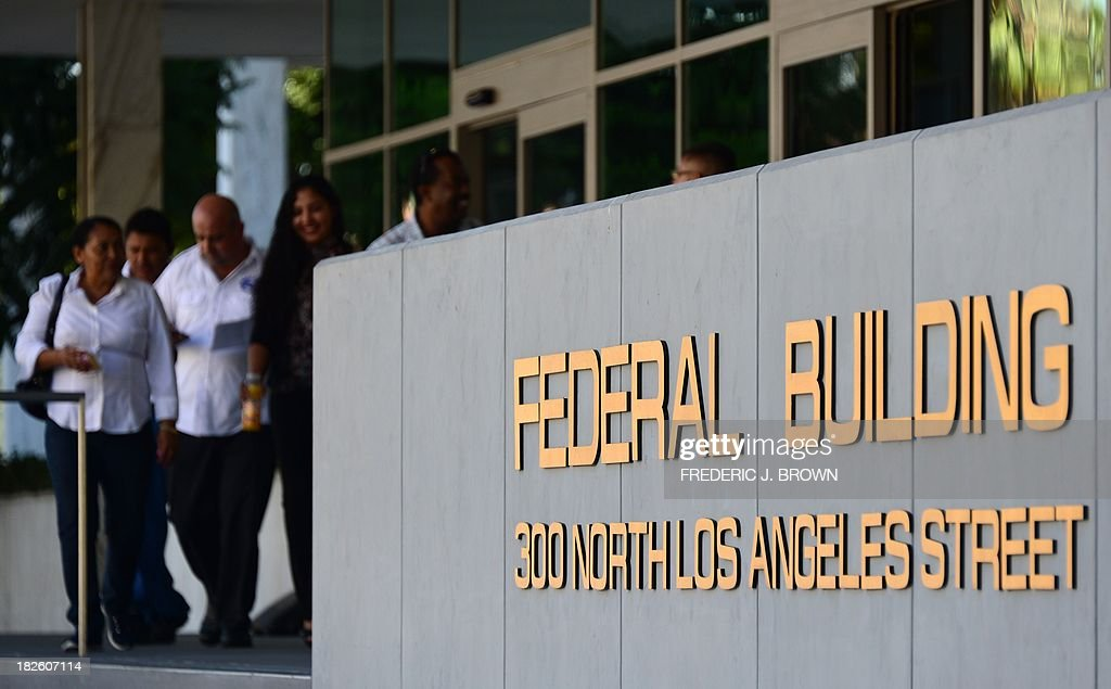 People walk past a federal building in Los Angeles where immigration services remained open but not the office of the Internal Revenue Service, frustrating those who arrived only to find services closed, on October 1, 2013 in Los Angeles, California. US monuments closed, offices fell silent and 800,000 public servants were told to stay at home on Tuesday as Washington's perennial political crisis forced the first government shutdown in 17 years. AFP PHOTO/Frederic J. BROWN