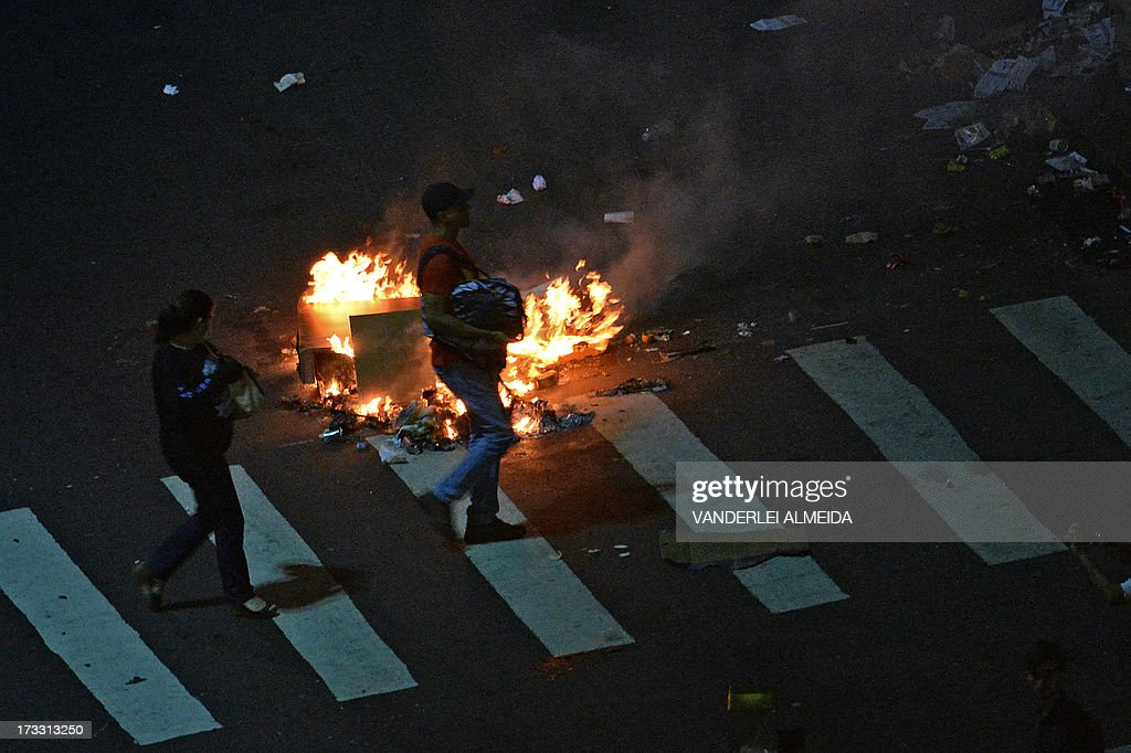 People walk past a fire set by demonstrators in the middle of a street after clashes erupted following a march by Brazilian workers in Rio de Janeiro on July 11, 2013 in a day of industrial action called by major unions to press demands for better work conditions. Demonstrators on Thursday blocked roads and staged protest rallies across the country on the 'National Day of Struggles' which was called by the country's five leading labour federations during last month's mass street protests to demand better public services and an end to endemic corruption.