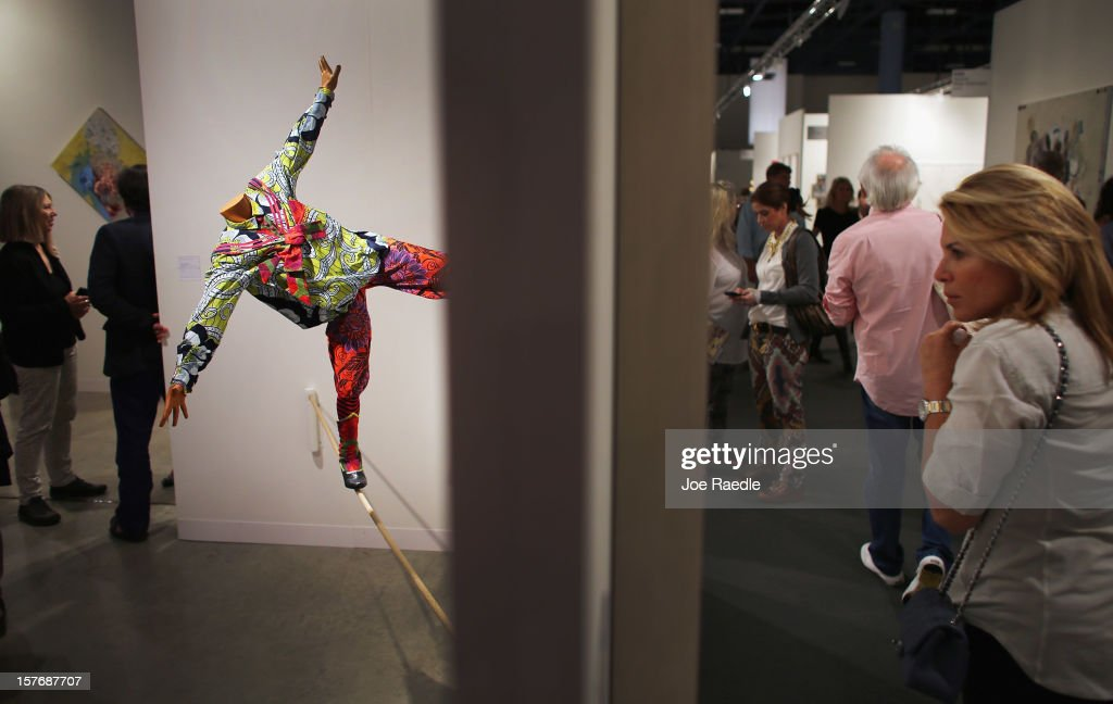 People walk past a gallery with an art piece titled, 'Boy on Tightrope' by Yinka Shonibare as Art Basel opens at the Miami Beach Convention Center on December 5, 2012 in Miami Beach, Florida. The 11th edition of the art show runs from December 6 through the 9th.