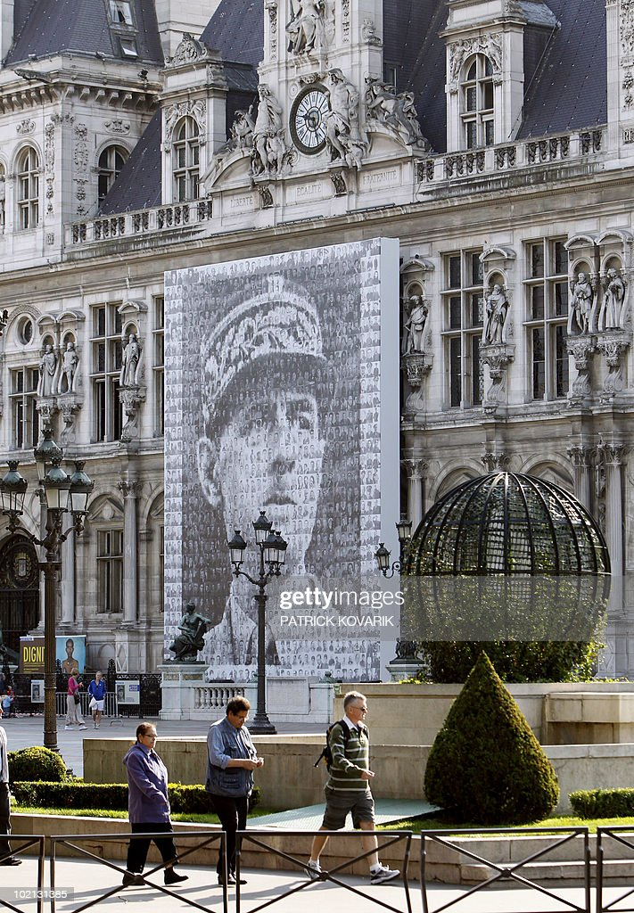 People walk past a giant banner (13x16 meters) representing France's general Charles de Gaulle on the facade of Paris townhall on June 16, 2010, as part of the commemorations for the 70th anniversary of De Gaulle stirring appeal to resist Nazism from London on June 18, 1940. The banner is a giant mosaic of 1016 portraits of Compagnons de la Liberation (French resistance members during WWII).
