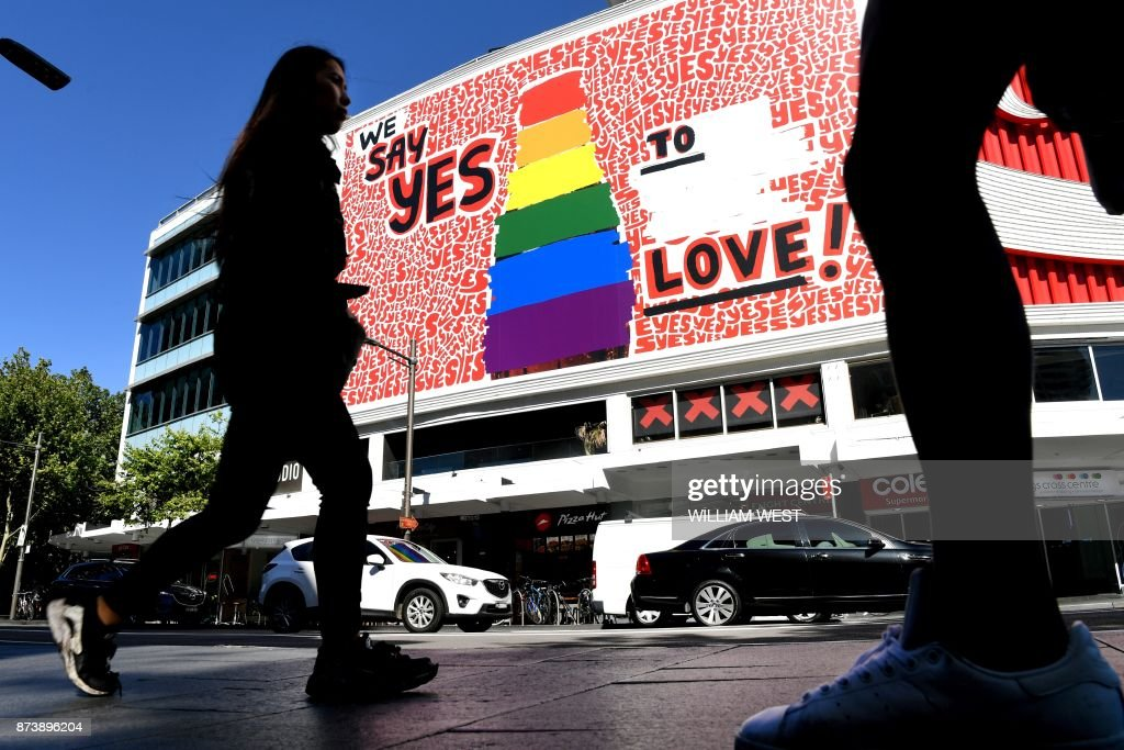 People walk past a giant billboard in Sydney's Kings Cross district promoting the 'yes' vote for same-sex marriage on November 14, 2017. Debate on same-sex marriage is set to move from Australian streets to the parliament when the results of a contentious national vote are announced, with 'yes' supporters hopeful for a win. / AFP PHOTO / William WEST / TO GO WITH Australia-politics-marriage-rights-gay, ADVANCER by Glenda KWEK
