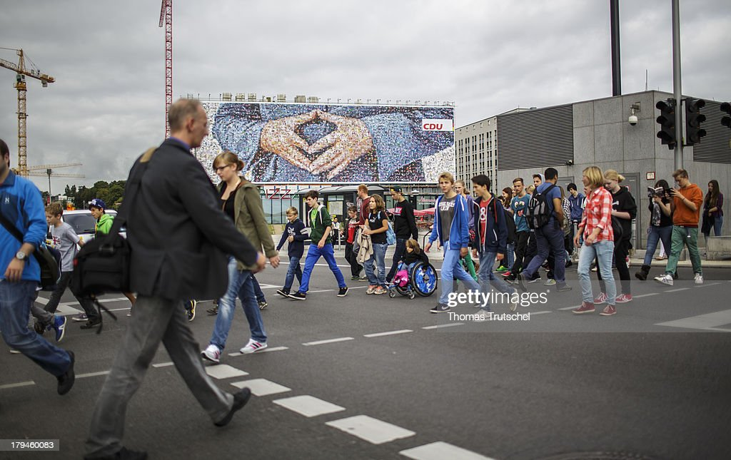 People walk past a giant election campaign poster featuring a pair of hands which are meant to represent German Chancellor and Christian Democrat (CDU) Angela Merkel and a stance she has become known for, is seen near Berlin Central Station on September 04, 2013 in Berlin, Germany. Germany is facing federal elections scheduled for September 22 and so far Merkel and the CDU have a substantial lead in polls over the opposition.
