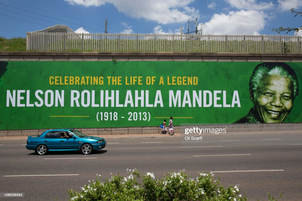 People walk past a giant poster of Nelson Mandela as the former South African president lies in state for a final day at Union Buildings on December 13, 2013 in Pretoria, South Africa. Over 60 heads of state have travelled to South Africa to attend a week of events commemorating the life of former South African President Nelson Mandela. Mr Mandela passed away on the evening of December 5, 2013 at his home in Houghton at the age of 95. Mandela became South Africa's first black president in 1994 after spending 27 years in jail for his activism against apartheid in a racially-divided South Africa.