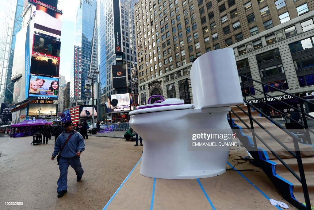people walk past a giant toilette that is part of a promotional campaign for a diaper company on Times Square, in New York, January 29, 2013. AFP PHOTO/Emmanuel Dunand