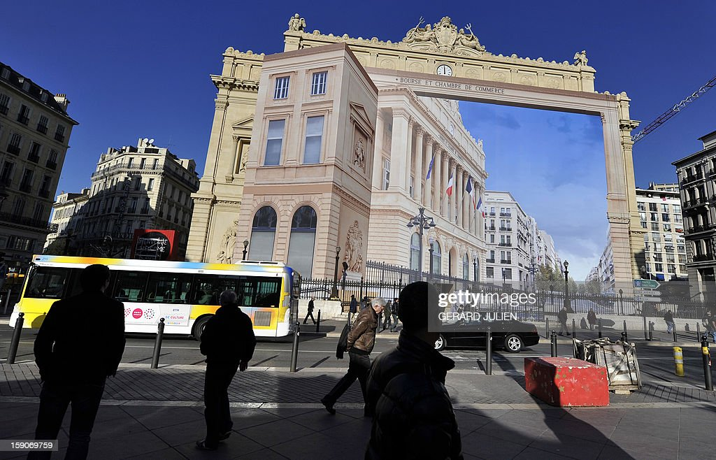 People walk past a giant trompe-l'oeil by artist Pierre Delavie set up on the facade of the Palais de la Bourse building in Marseille, southern France, on January 7, 2013, as part of 'Marseille-Provence European Capital of Culture' in 2013.