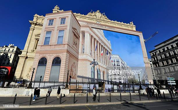 People walk past a giant trompel'oeil by artist Pierre Delavie set up on the facade of the Palais de la Bourse building in Marseille southern France...