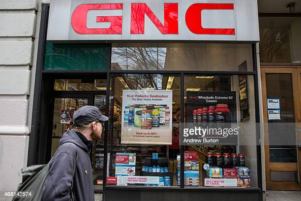 People walk past a GNC store on March 30 2015 in New York City GNC in alliance with New York State Attorney General Eric Schneiderman announced new...