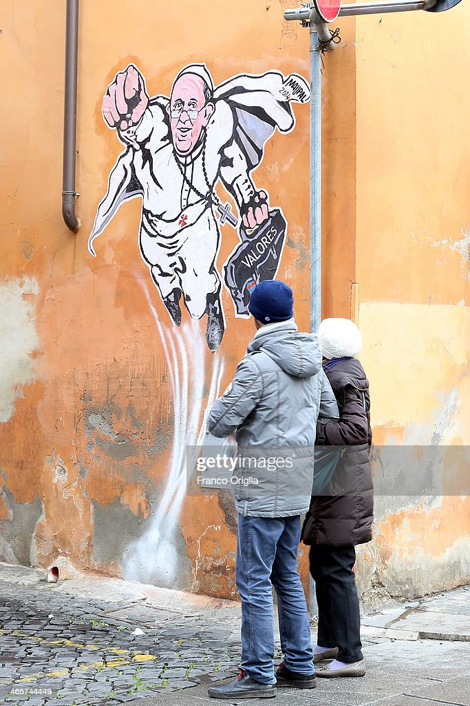People walk past a graffiti featuring a 'superhero' version of Pope Francis appears in Borgo Pio, next to St. Peter's Square on January 29, 2014 in Rome, Italy. The image started circulating from the twitter account of the Vatican and has rapidly spread around the world.