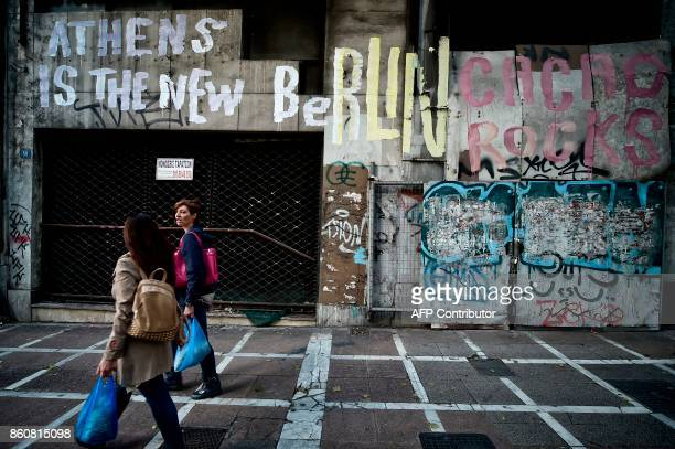 People walk past a graffiti reading 'Athens is the new Berlin' by street artist Cacao Rocks on the wall of an old neoclassical building in central...